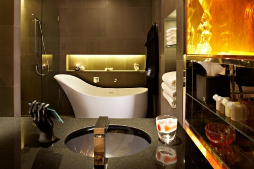 The dark stone bathrooms are accented by oversized signature baths and large separate showers with pin-spot lighting.